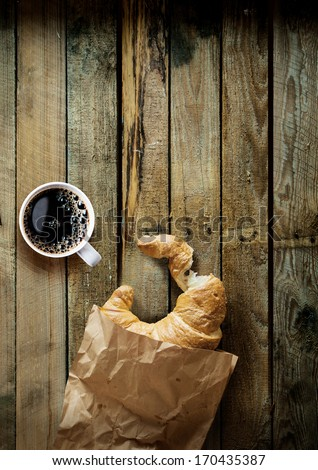 Coffee break in the country with a cup of freshly brewed espresso coffee and a bitten croissant in a crumpled brown paper bag on a grungy weathered table top with copyspace - stock photo