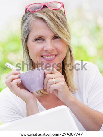 coffee break of cute mature blond working at home in her garden - stock photo