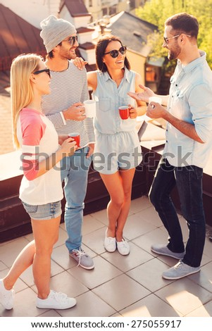 Coffee break on the roof. Top view of four young cheerful people chatting and drinking coffee while standing on the roof terrace together - stock photo