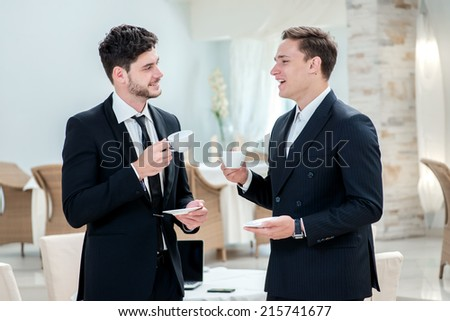 Coffee break. Two other businessman drinking coffee and talking to each other while standing in an office and smiling to each other - stock photo