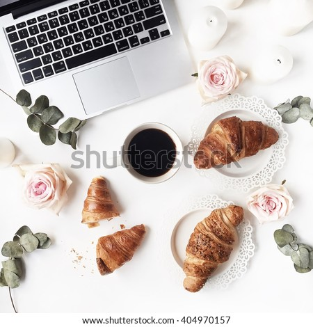 Coffee break with laptop, croissants, pink rose flower, petals, candles, vintage plates and black coffee composition. Flat lay, top view - stock photo