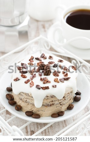 coffee cake with icing decorated with cocoa beans, top view, close-up - stock photo