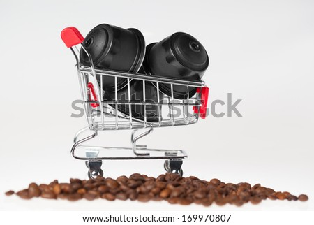 Coffee capsules in a small shopping cart in coffee grains on white background. - stock photo