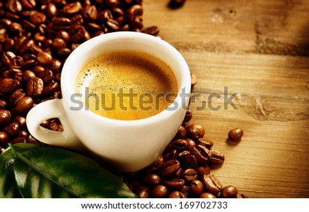 Coffee. Coffee Espresso. Cup Of Coffee with Beans and Green Leaf on a Wooden Background. Border Design  - stock photo
