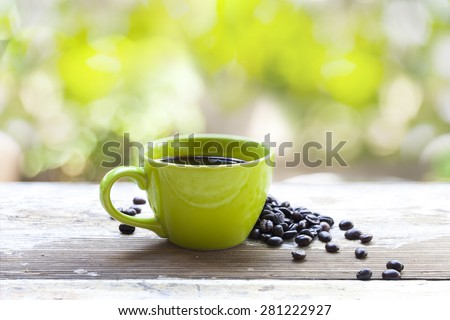 coffee cup and beans by the garden - stock photo