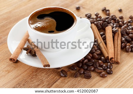 Coffee cup and beans, cinnamon sticks, anise on wooden table - stock photo