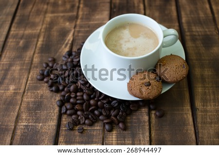coffee cup and beans  on wooden table on brown background - stock photo