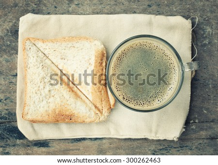 coffee cup and bread on old wooden table.Vintage Style - stock photo