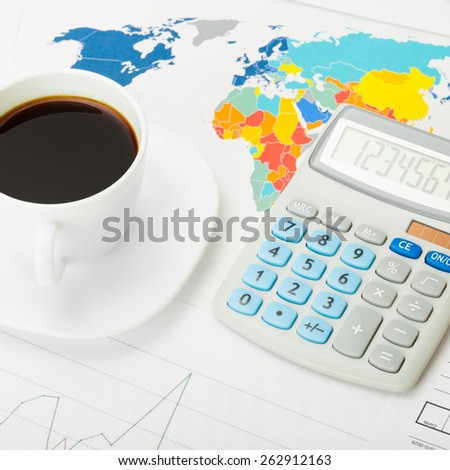 Coffee cup and calculator over world map and some financial charts - stock photo