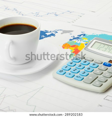 Coffee cup and calculator over world map and some financial charts - close up shot - stock photo