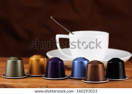 coffee cup and capsules on a wooden table - stock photo