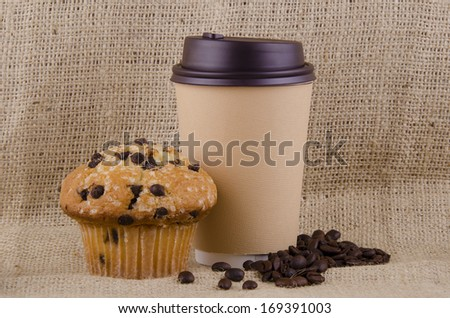 Coffee cup and chocolate chips muffin on jute background. - stock photo