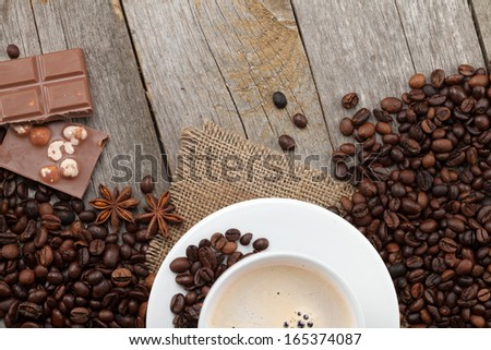 Coffee cup and chocolate on wooden table texture with copy space. View from above - stock photo