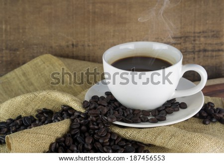 Coffee cup and coffee beans on old wooden background - stock photo