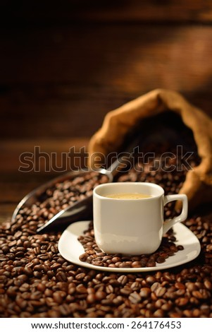 Coffee cup and coffee beans on old wooden table - stock photo