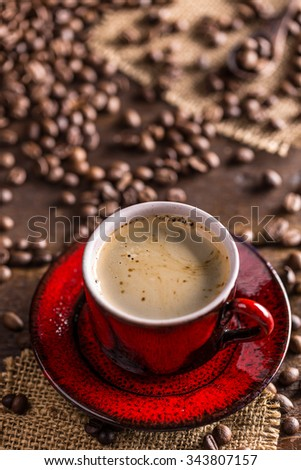 Coffee cup and coffee beans on rustic background - stock photo