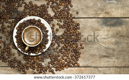 Coffee cup and coffee beans on table - stock photo