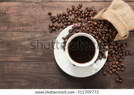 Coffee cup and coffee beans on wooden background. Top view. - stock photo
