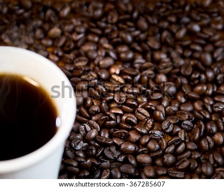 Coffee Cup and Coffee Beans.  Space for Text/copy space.  Features coffee beans spread across the photo, with slightly out of focus white coffee cup in the corner.  - stock photo