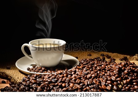 Coffee cup and coffee beans with smoke on burlap sack - stock photo