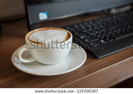 Coffee cup and computer on table - stock photo