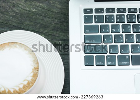 Coffee cup and laptop business on wood table - stock photo