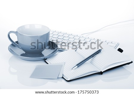 Coffee cup and office supplies. Blue toned - stock photo