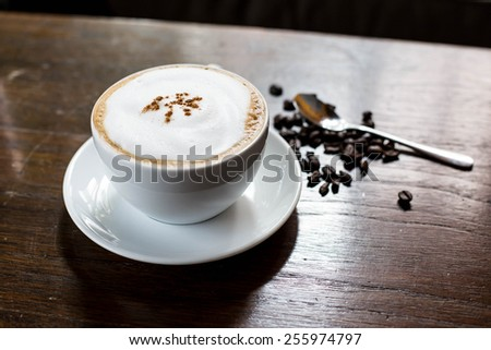 Coffee cup and saucer on a wooden table - stock photo