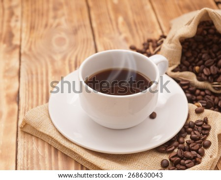 Coffee cup and saucer on a wooden table. Dark background. - stock photo