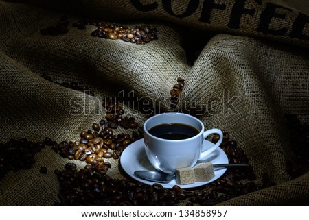 Coffee cup, beans and burlap. still life - stock photo