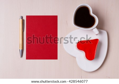 Coffee cup jelly cake in form of heart and red paper blank with pen on wooden surface, top view copy space for text - stock photo