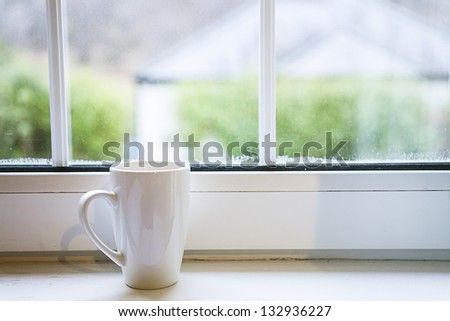Coffee cup near window - stock photo