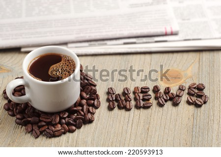 Coffee cup, newspaper and the word news on wooden table - stock photo