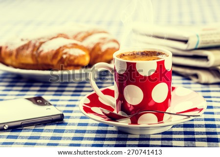 Coffee. Cup of coffee. Dotted cup of coffee, two sweet croissants, paper newspapers, mobile phone on blue checkered tablecloth. Coffe breack. Breakfast at my mother or  grandmother.  - stock photo
