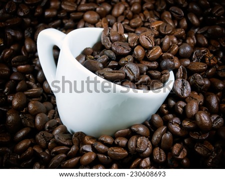 Coffee cup on a pile of whole coffee beans. - stock photo
