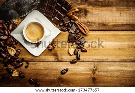 Coffee cup on a wooden table among coffee beans  and dark chocolate  - stock photo
