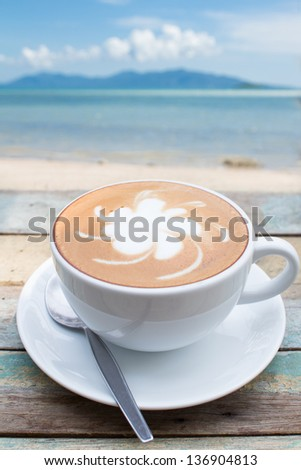 Coffee cup on terrace facing seascape - stock photo