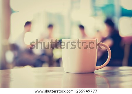 Coffee cup on the table with people in coffee shop as blur background - vintage (retro) style color effect - stock photo
