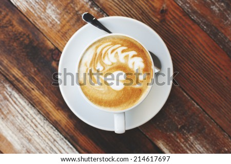Coffee cup on wooden table, artistic photo - stock photo