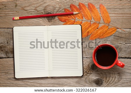 Coffee cup, open diary, pencil and autumn leaves on wooden background - stock photo