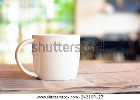 Coffee cup over newspaper on the table in blurred coffee shop background - stock photo