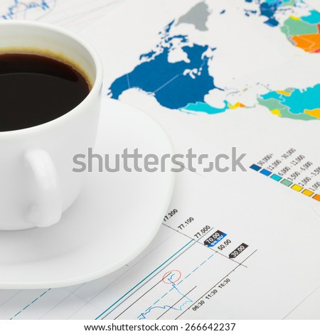 Coffee cup over world map and financial market chart - close up shot - stock photo