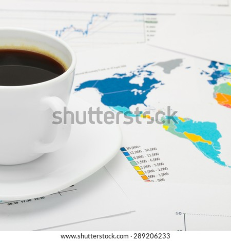 Coffee cup over world map and some financial documents - close up shot - stock photo