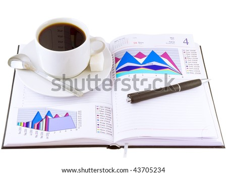 Coffee cup, pen, standing on the open personal organizer and  financial  diagrams  on a pages.Isolated. - stock photo