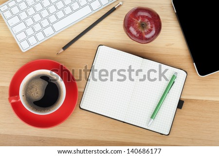 Coffee cup, red apple and office supplies on wooden table - stock photo