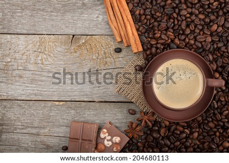 Coffee cup, spices and chocolate on wooden table texture with copy space. View from above - stock photo