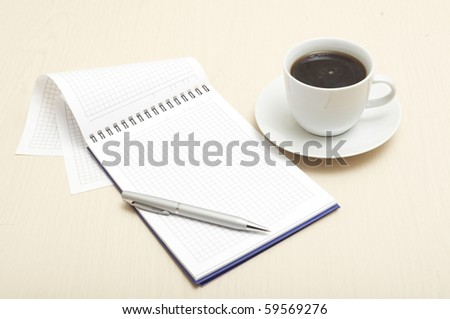 Coffee cup, spiral notebook and pen on the wooden table - stock photo