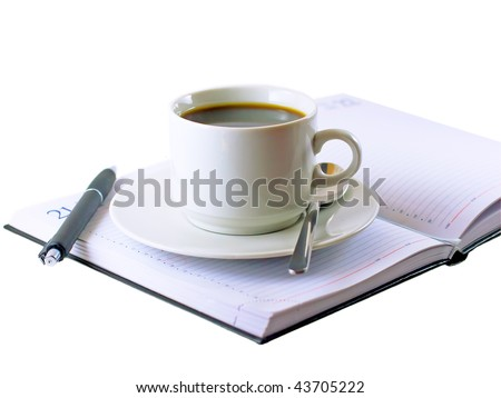 Coffee cup, the handle standing on the opened daily organizer . Isolated - stock photo