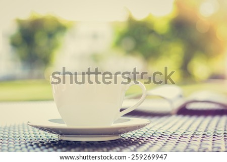 Coffee cup with book  on the table in blurred green nature background - vintage style colors - stock photo