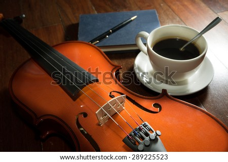 Coffee cup with book,pen and violin. - stock photo